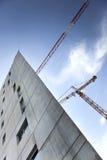Moderna byggnad och kranar Arkivfoto