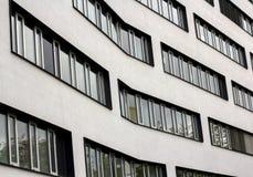 Moderna fönster i rad på en krökt byggnad Textur av arkitektonisk urbanisering Gatafotografi i stilen av minimalism arkivbild