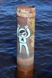 Moderna grafitti på ett metallrör i mitt av floden från de unga vandalerna arkivbild