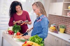 Moderna kvinnor, matlagning och gyckel i köket arkivfoton