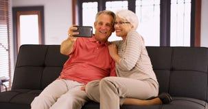 Moderna morföräldrar som hemma tar selfies arkivbild