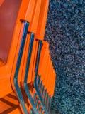 Moderna orange plast-- och kromstolar som utomhus staplas upp arkivfoto