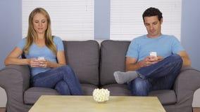 Moderna par genom att använda deras smartphones på soffan Royaltyfria Bilder