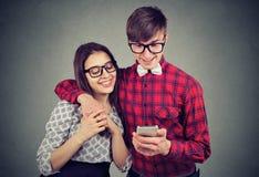 Moderna par genom att använda smartphonen tillsammans royaltyfri foto
