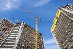 Moderna stads- byggnader under konstruktion med en kran och en blå himmel royaltyfri bild