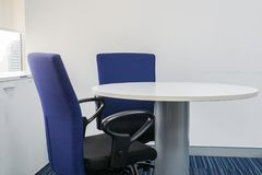 Moderna stolar och rund tabell för möte i regeringsställning Arkivbild