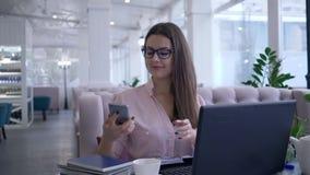 Moderna teknologier i utbildning, den lyckade unga kvinnlign gör selfiefotoet på smartphonen under arbete på bärbara datorn och arkivfilmer