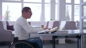 Moderna teknologier i utbildning, student som handikapp på hjulstol som arbetar med bärbara datorn för att lära från online-under arkivfilmer