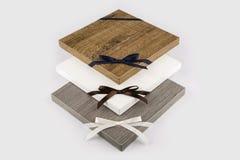 Moderna tre köksluckor på den vita tabellen Vita köksluckor Tränaturliga bruna köksluckor Gråa köksluckor Royaltyfri Foto