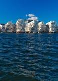 Moderna vita byggnader på det blåa vattnet royaltyfri foto