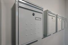 Moderna vita metalliska postaskar för en lägenhet i rad mot en vit målad vägg med nummer på dem och lås royaltyfri fotografi