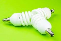 Moderna vridna lightbulbs på grön backgound Arkivbild