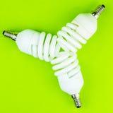 Moderna vridna lightbulbs på grön backgound Fotografering för Bildbyråer