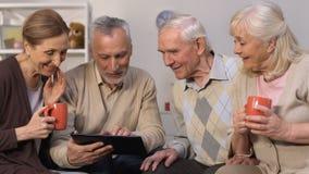Moderne ältere Freunde, die App auf der Tablette ein Bankkonto habend, lächelnd an der Kamera, Gerät verwenden stock video footage