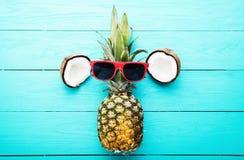 Moderne ananas met zonnebril en kokosnoot op blauwe houten achtergrond Hoogste mening Stock Foto