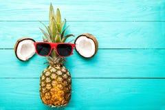 Moderne ananas met zonnebril en kokosnoot op blauwe houten achtergrond Hoogste mening Royalty-vrije Stock Fotografie