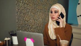 Moderne Arabische bedrijfsvrouw die aan laptop werken en op een smartphone spreken stock videobeelden