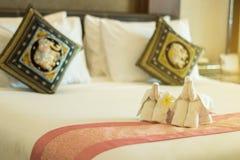 Moderne Art des Schlafzimmers mit gefaltetem Tuch in der Elefantform auf Bett Stockfoto