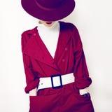 Moderne Art schöner Weinlesedame in einem roten Mantel und in einem Hut stockfotos