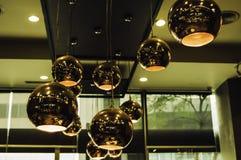 Moderne Artleuchter verkupfern die Farbe, die von der Decke innerhalb des Restaurants hängt, das vereinbart worden ist und der In stockfoto