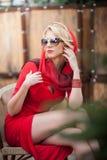 Moderne attraktive Dame mit rotem Kleid und dem Kopftuch, die auf Stuhl im Restaurant, Außenaufnahme am sonnigen Tag sitzt stockbilder