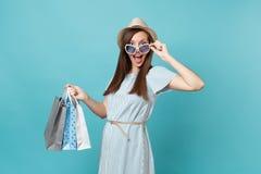 Moderne attraktive glückliche Frau des Porträts im Sommerkleid, Strohhut, Sonnenbrille, die Pakettaschen mit Käufen hält lizenzfreie stockfotografie
