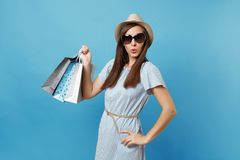Moderne attraktive glückliche Frau des Porträts im Sommerkleid, Strohhut, Sonnenbrille, die Pakettaschen mit Käufen hält lizenzfreie stockfotos