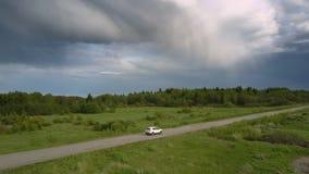 Moderne automobiele aandrijving langs grijze weg tegen bos stock footage