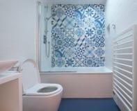 Moderne badkamers met bad, toilet, gebied in muur en bassineenheid, blauwe rubbervloer en blauwe en witte lapwerktegels stock afbeelding