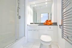 Moderne badkamers in witte grote doucheruimte Stock Afbeeldingen