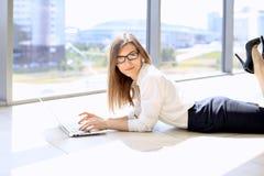 Moderne bedrijfsvrouw die met laptop computer werken terwijl het liggen bij de vloer in het bureau, exemplaarruimte Stock Foto