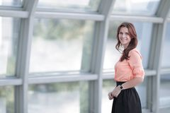 Moderne bedrijfsvrouw die zich dichtbij een groot venster in het bureau bevinden royalty-vrije stock afbeelding