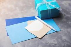 Moderne blaue Geschenkbox mit Umschlägen für Grußkarte auf konkretem Hintergrund Leere Karte mit weißem Stift Lizenzfreie Stockfotos