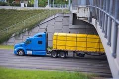 Moderne blauwe semi vrachtwagen met gele dekkingslading op aanhangwagen vlakke B royalty-vrije stock fotografie