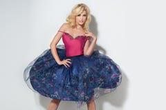 Moderne blonde Dame, die im Blumenrock aufwirft Lizenzfreies Stockfoto