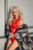 Moderne blonde Frau im Luxuspelzmantel trägt im sexy roten Gummilack Stockfotografie