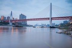 Moderne Brücke zur Sonnenuntergangzeit mit Stadthintergrund Stockfoto