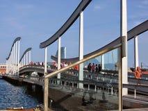 Moderne bridge on the Rambla de Mar to Barcelona in Spain. Blue clear sky. Sunny day. People on the bridge. Travel destination. Port of Barcelona. Platform on Royalty Free Stock Photography
