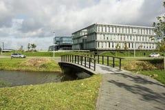Moderne bureaugebouwen op een economische sector in Nederland met kanaal, bomen, water, blauwe hemel, witte wolken en werven Royalty-vrije Stock Foto's