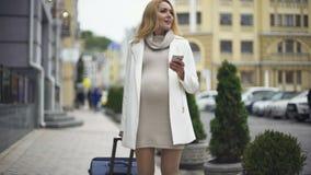 Moderne denkende vrouw die smartphonetoepassing gebruiken, die met koffer reizen stock video