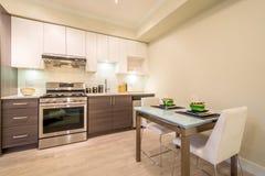 Moderne die eetkamerlijst voor diner met een keuken op de achtergrond wordt geplaatst stock foto's