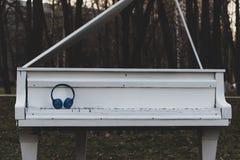 Moderne, drahtlose, blaue Kopfhörer liegen auf einem weißen, hölzernen, alten Klavier, am Abend bei Sonnenuntergang in einem Park stockbilder