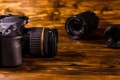 Moderne dslr Kamera und Linsen auf Holztisch lizenzfreie stockbilder