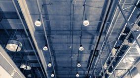 Moderne dubbele verhaalruimte in zwart-wit kleurentoon met aardlichten van van de dakdek en muur het hangen onderaan lichte lamp stock afbeeldingen