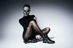 Moderne dunkle Frau, die auf dem Boden sitzt Stockfoto