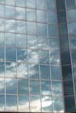 Moderne errichtende Glasfassade, die bewölkten blauen Himmel reflektiert Stockbild