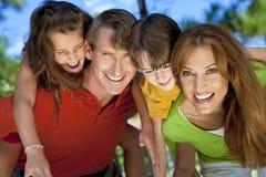 Moderne Familie, die Spaß in einem Park hat Lizenzfreie Stockbilder