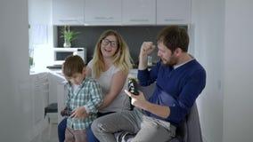 Moderne familie, mamma met zoon en papa het spelen in videospelletjezitting op stoel stock video