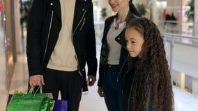 Moderne Familie mit einem Kind schließen Käufe in einem modernen Einkaufszentrum ab stock video footage