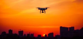 Moderne Fernsteuerungsluft-Brummen-Fliege hoch mit Aktionskamera im Sonnenunterganghimmel Lizenzfreies Stockfoto